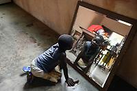 TOGO, Tohoun, orphanage, girl looking in mirror / Waisenhaus, Maedchen schaut in den Spiegel