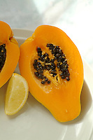 Plate of ripe papaya fruit with lemon wedge