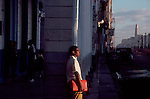 Cuba, Havana, A young student awaits public transportation in Central Havana with the harbor and Morro Castle in the distance.