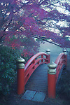 Arched red bridge in a Japanese garden, misty autumn scenery in Kyoto, Japan Image © MaximImages, License at https://www.maximimages.com