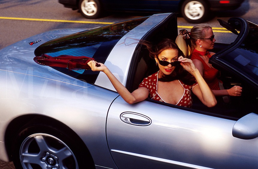 A flirtatious young woman lets her scarf blow in the wind as she rides with a friend in a silver Corvette convertible.