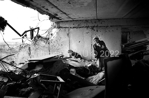 Grozny, Chechnya.1995.A man and his wife go through what is left of their apartment looking for goods that may have survived the bombing and the looting. His 8th floor apartment lays in ruins and he was shot at by Russian soldiers the last time he tried enter it.
