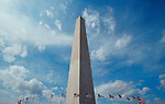 American flags flying at the base of the Washington Monument frame the monolith with a blue sky, whitle cloud backdrop, Washington DC, USA