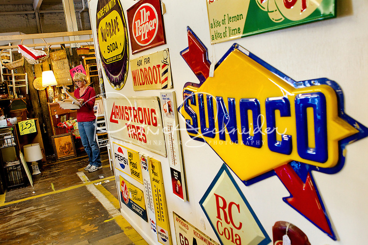 Shopper Melissa Woodring of Boone, North Carolina looks through the thousands of unique items available for purchase at the Depot at Gibson Mill. The Depot at Gibson Mill, an antique and designer mall that was once a mill, located in Concord, N.C. With 85,000 square feet and 460 booths, we have quickly become the largest antique and designer mall in the South. Once a part of the old Cannon Mills, the charm of the 20 foot ceilings, wide wooden floors and exposed brick remains. Photo is part of a photographic series of images featuring Concord, NC, by Charlotte-based photographer Patrick Schneider..