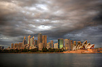 View on the  Opera House and Sydney CBD from the Sydney Harbour, early in the morning with a cloudy sunrise.