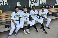 Columbia Fireflies players Edgardo Fermin (10), Jay Jabs (21), Hansel Moreno (12) and Jose Brizuela (20) pose for a photo in the dugout before a game against the Charleston RiverDogs on Tuesday, August 28, 2018, at Spirit Communications Park in Columbia, South Carolina. Columbia won, 11-2. (Tom Priddy/Four Seam Images)