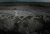 Una inmensa mancha roja cubre la esquina suroeste de España. Los atlas con los índices de mortalidad por cáncer del Instituto Carlos III muestran una.terrorífica tasa de muerte por diferentes tipos de tumores en la comarca de Huelva. Los científicos sólo encuentran una explicación a esta acumulación imparable y espeluznante de muertes. Una inmensa mancha cubre un extremo de la ciudad. Es más grande que la.misma ciudad, Huelva. Son los residuos de los fosfoyesos. Encorsetada geográficamente por esta balsa y un tremendo polo petroquímico, la muerte es una realidad que se calla. Es una vecina más, junto a decenas de.enfermedades endémicas por contaminación. (C) Pedro ARMESTRE