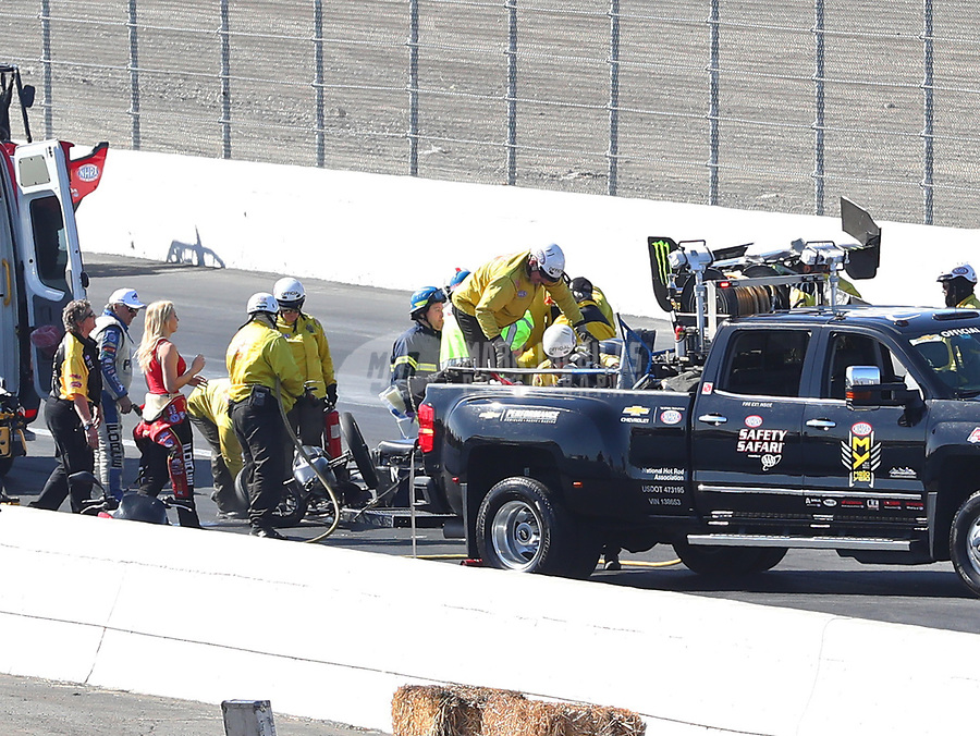 Feb 11, 2018; Pomona, CA, USA; NHRA funny car driver John Force (left) and Courtney Force look on as the safety safari rescue crews tend to his daughter, top fuel driver Brittany Force after crashing during round one of the Winternationals at Auto Club Raceway. Mandatory Credit: Mark J. Rebilas-USA TODAY Sports