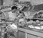 "Bethel Park PA:  View of a woman selecting produce at Bethel Market Grocery Store.  Marjorie Stewart is shopping for produce during an onsite photography assignment for Bethel Market.  Bethel Market was ""the"" neighborhood grocery store in Bethel Park from the late 1950s through the early 1980s."