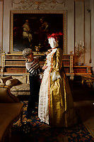 """BNPS.co.uk (01202 558833)<br /> Pic: ZacharyCulpin/BNPS<br /> <br /> Denise applies the finishing touches to a costume in one of the many grand rooms in Uppark <br /> <br /> Ori-garments -  Artist Denise Watson has created a stunning 1750's masquerade Christmas Ball with characters made entirely from paper at the National Trust's Uppark House in West Sussex.<br /> <br /> Denise has dressed 14 shop mannequins with clothes, shoes, masks, fans, floral details, hair and even jewellery made from things like tissue paper, gift wrap and brown parcel paper. <br /> <br /> The festive display was inspired by Admiral Lord Gambier's memoirs in which he quotes from Lady Sarah Featherstonhaugh's journal of 1753 where she wrote: """" The whole party afterwards proceed to Uppark, where they passed a cheerful happy Christmas in the most friendly society, and enlivened their neighbourhood with some masked balls.""""<br />  <br /> The design to the finished result took a total of three months. Denise said, """"I am really delighted with the final result. It has been a joy to work at Uppark using the grand rooms and to recreate an event which actually took place""""."""