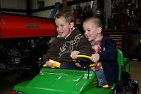 Aidan & Eli taking their first test spin in a kiddie John Deere.