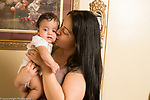 4 month old baby girl turning face away as mother kisses her cheek