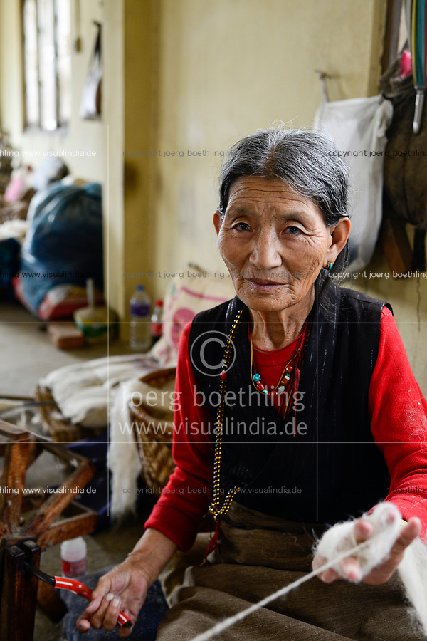 NEPAL Kathmandu, Lalitpur, tibetische Fluechtlinge, tibetisches Fluechtlingslager Jawalakhel, Teppichfabrik JHC Jawalakhel Handicraft Center, tibetische Frauen spinnen die Wolle, Frau Kunsang, 72 Jahre