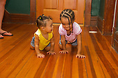 MR / Schenectady, NY. Toddler (girl at right, 2, African American & Caucasian) crawling on the floor next to her baby sister (infant at left, 10 months, African American & Caucasian). MR: Dal4, Dal5. ID: AL-HD. © Ellen B. Senisi