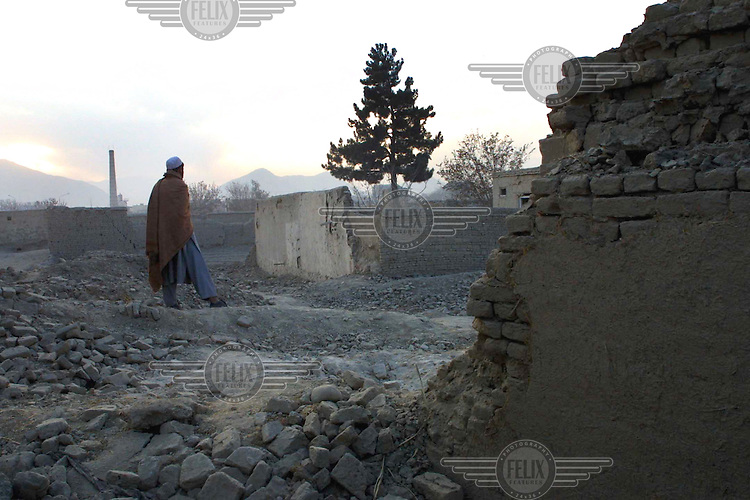 AFGHANISTAN. Kabul. 29 Nov 2001..A neighbour stands amongst the remains of three houses that were hit by a US bomb in October in the Qala Zaman Khan area of Kabul. Five members of one family were killed and three members of another were wounded in the explosion..© Andrew Testa / Panos Pictures