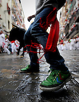 Participants run in front of Miura bulls during the first San Fermin Festival bull run, on July 8, 2012, in Pamplona, northern Spain. The festival is a symbol of Spanish culture that attracts thousands of tourists to watch the bull runs despite heavy condemnation from animal rights groups . (c) Pedro ARMESTRE