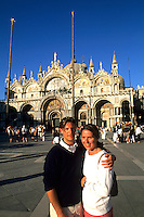 Young 20s European tourist couple brightly dressed in front of the Famous St Marks Church in San Marcos Plaza in romantic Venice Ital
