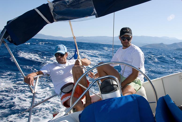 To sailors man a private boat in the Mediterranean Sea off the Greek island of Crete.
