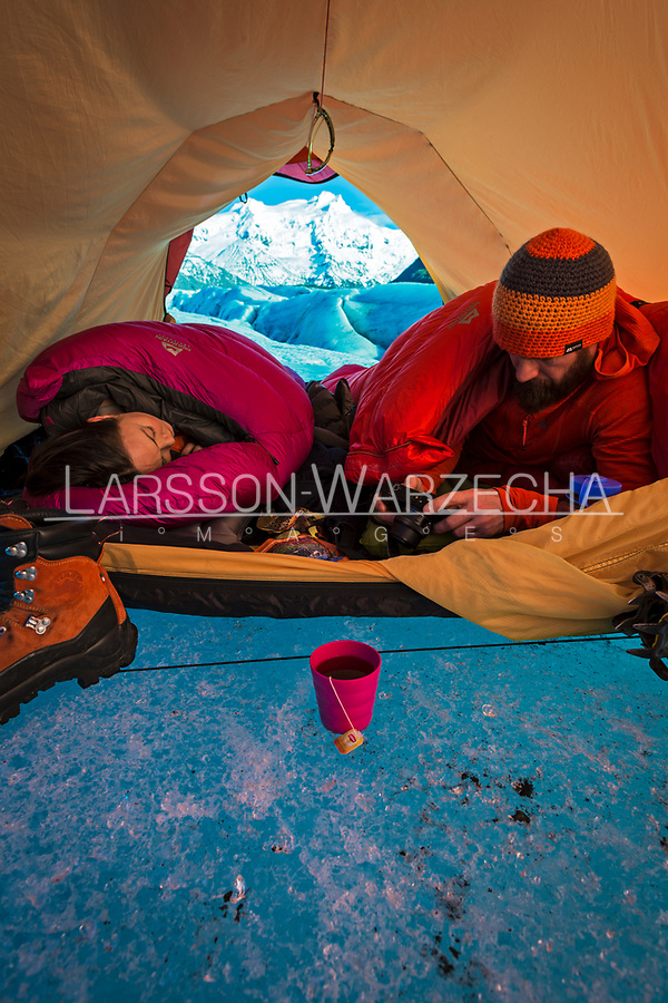 Male and female hikers camp on a glacier, Iceland