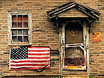 An abandoned store, long ago demolished displays an American Flag.