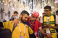 MOSCOW, RUSSIA - June 26, 2018: A Denmark fan talks with Australia fans on Nikolskaya Street during the 2018 FIFA World Cup. The street was a crossroads for foreign soccer fans and local Russians during the World Cup in Russia.