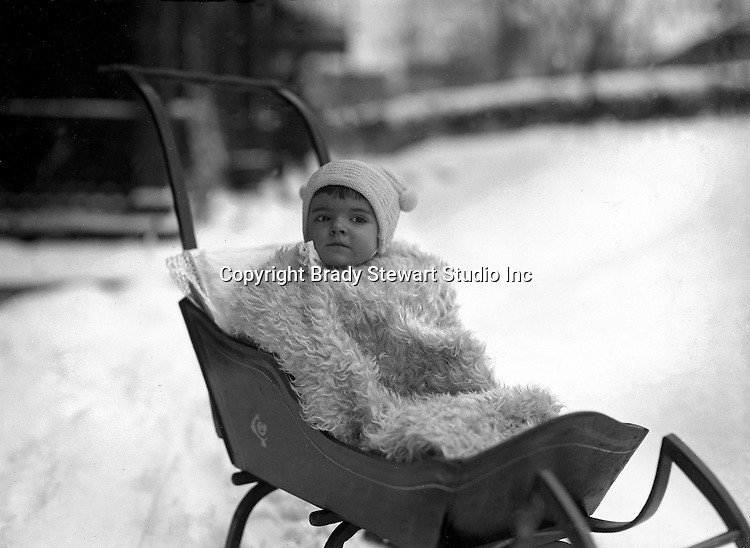 Product: Antique Child's Push Sleigh<br /> <br /> 1Wilkinsburg PA: Helen Stewart bundled in a blanket and hat while riding in a baby sleigh.
