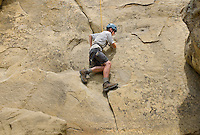 Photo story of Philmont Scout Ranch in Cimarron, New Mexico, taken during a Boy Scout Troop backpack trip in the summer of 2013. Photo is part of a comprehensive picture package which shows in-depth photography of a BSA Ventures crew on a trek.  In this photo BSA Venture Crew Scout climbs across the natural rock face at Dean Cow Camp, in the backcountry at Philmont Scout Ranch.   <br /> <br /> The  Photo by travel photograph: PatrickschneiderPhoto.com