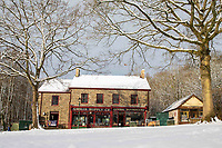 Cardiff, Wales, UK. 1st February 2019. A man and dog walk past traditional old fashioned Welsh shops at St Fagans National Museum of History in Cardiff while a man clears snow as freezing temperatures strike much of the UK during a winter cold snap.
