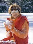 Deutschland, Frau sitzt im Schnee mit Schneeball | Germany, woman with snowball sitting in the snow
