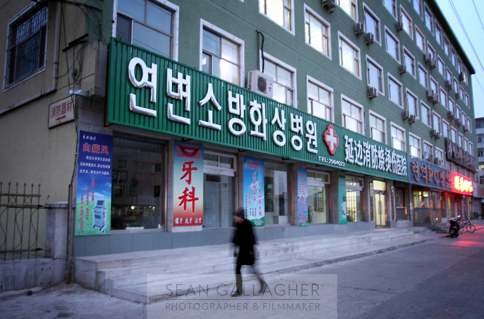 China. Jilin Province. Storefronts in the town of Yanji, close to the border with North Korea. The town is part of the Korean Autonomous Prefecture in the north-east of the country, hence many signs are in both Chinese and Korean. 2011