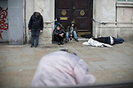 © Joel Goodman - 07973 332324 . 06/04/2017 . Manchester , UK . A group of men huddle in a doorway on Piccadilly Gardens , one lies in an unresponsive state on the pavement , another stands slouched back against the wall and another man is slouched over on a bench opposite . An epidemic of abuse of the drug spice by some of Manchester's homeless population , in plain sight , is causing users to experience psychosis and a zombie-like state and is daily being witnessed in the Piccadilly Gardens area of Manchester , drawing large resource from paramedic services in the city centre . Photo credit : Joel Goodman
