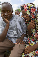 Rwanda. Southern province. Murambi. Couple at the 13th commemoration of the Genocide. The vwoman is wearing a colorful veil on her head, the man a black & white t-shirt with the face of a woman. The site of Murambi is located in the district of Nyamagabe, in the former Gikongoro prefecture, Nyamagabe commune. The site of Murambi is intented to be a regional research and documentation centre on Genocide. A special memory place where over 50'000 people perished on the site.  © 2007 Didier Ruef