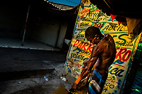 An Afro-Colombian homeless man tears out cardboards in front of the wall, covered with Champeta music propaganda, in the market of Bazurto in Cartagena, Colombia, 5 December 2018. Far from the touristy places in the walled city, a colorful, vibrant labyrinth of Cartagena's biggest open-air market sprawls to the Caribbean seashore. Here, in the dark and narrow alleys, full of scrappy stalls selling fruit, vegetables and herbs, meat and raw fish, with smelly garbage on the floor and loud reggaeton music in the air, the African roots of Colombia are manifested.