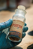 A hazardous waste worker holds an aging container labeled as poison after it was dropped off at a hazardous waste disposal site in Westerville, Ohio. Homeowners were able to remove any hazardous waste from their homes to be properly recycled or disposed of instead of placing in their trash or pouring down the drain.<br />