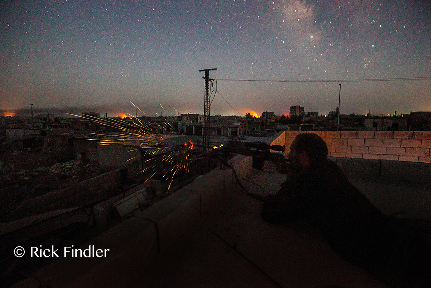 August 2017. YPG Media Centre, Raqqa, Syria.<br /> Foreign volunteer fighter 'Macer Gifford' shoots his sniper rifle at ISIS positions in the late hours of the evening.<br /> The MFS (Syriac Military Council) are a group of Assyrian Christians who fight alongside the Syrian Democratic Forces in the fight to topple ISIS.<br /> Photographer: Rick Findler