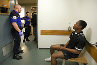 """Switzerland. The Republic and Canton of Neuchâtel. Neuchâtel. Police station headquarters. """"Narko"""" operation. The narcotics squad has arrested a black man from Western Africa. He sits in a cell among a group of policemen and policewoman (some with blue uniforms, another in plein-clothes). The man was catched while selling illegal substances (cocaine drugs). Plainclothes law enforcement is a method used by police. The policemen wear plainclothes or """"ordinary clothes"""" instead of a uniform in order to avoid detection or identification as law enforcement agents. Police officers in plainclothes must identify themselves when using their police powers. A police station or station house is a building which serves for police officers. The building contains temporary holding cells and interview/interrogation rooms. 1.04.15 © 2015 Didier Ruef"""