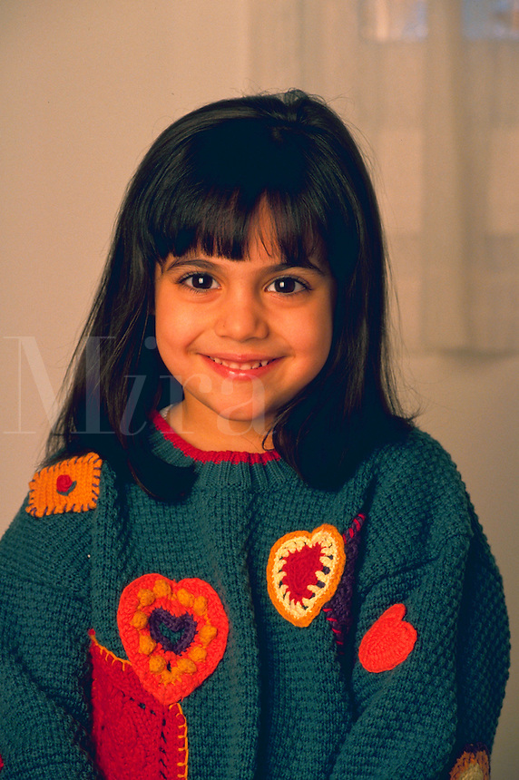 Portrait of smiling young girl with dark brown eyes.