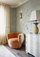 A stylish bedroom decorated in Chinoiserie wallpaper with a yellow floral and bird pattern. An orange tub chair stands in the corner next to a chest of drawers