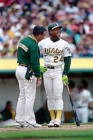 OAKLAND, CA - Rickey Henderson of the Oakland Athletics grimaces in pain and is tended to by team trainer Barry Weinberg at home late during a game at the Oakland Coliseum in Oakland, California in 1990. Photo by Brad Mangin