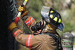 A firefighter using an ax on a structure fire with water being  sprayed on the fire