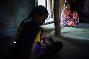 Rekha RAMESH nurses her son, Prahlad RAMESH as The local health worker, Shabjaan Fakira Wadhey sits in the house of their house in Dhawati VIllage of Khaknar block of Burhanpur district in Madhya Pradesh, India.  Photo: Sanjit Das/Panos for ACF