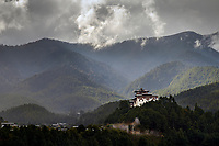 Light bursts through heavy rain clouds illuminating Jakar Dzong and the steep forested mountains of the Himalayan foothills