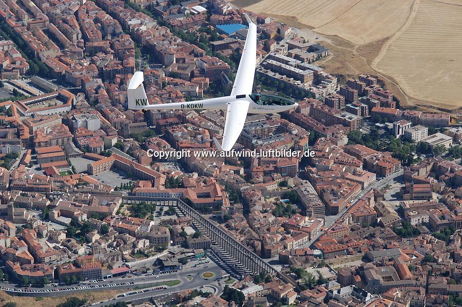 4415/Segelflugzeug ueber Segovia:SPANIEN, SEGOVIA, 26.07.2003:Selbststartendes Segelflugzeug vom Typ DG 800 B, Kunststoffsegelflugzeug mit 18 Meter Spannweite der Firma DG Flugzeugbau Bruchsal, Flugzeug ueber Segovia..Segovia ist eine Stadt in Spanien mit etwa 55.000 Einwohnern und zugleich der Verwaltungssitz der gleichnamigen Provinz Segovia in Kastilien-León. Die Stadt liegt etwa 90 Kilometer nordnordwestlich von Madrid auf einer 1.000 Meter hohen Felszunge zwischen den Flüssen Eresma und Clamores...Die Altstadt ist besonders sehenswert. Neben zahlreichen Monumenten ragen insbesondere die spätgotische Kathedrale von Segovia (1525 durch Auftrag Karls V. wiedererrichtet), das berühmte 28 Meter hohe und 728 Meter lange antike römische Aquädukt (aus dem 1./2. Jahrhundert n. Chr.) und die märchenhafte Palastfestung, der sog. Alcázar, der sich über der Stadt und der umgebenden Landschaft erhebt. Die Stadt gehört seit 1985 zum UNESCO-Weltkulturerbe. Die Kirche La Vera Cruz war seit 1208 bis zu seiner Zerschlagung eine Kirche des Tempelritterordens...Historisch war die im Jahr 80 v. Chr. gegründete Stadt von 714 bis ins 11. Jahrhundert maurische Besitzung. Erst Alfons VI. konnte die Stadt 1085 erobern, die zwischen dem 13. und 15. Jahrhundert Königsresidenz war. 1474 wurde hier Isabella zur Königin von Kastilien ausgerufen....Der Aquädukt, der bis ins 19. Jahrhundert hinein die Wasserversorgung regelte, wurde im 1. Jahrhundert n. Chr. von den Römern angelegt, die das antike Segobria in einen bedeutenden Militärstützpunkt verwandelten. Die Granitblöcke wurden ohne Mörtel aufeinander gesetzt. Die Pfeiler erreichen eine Höhe von 29 Metern..