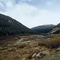 A river valley winds its way between snow-capped mountains covered in thick pine forests