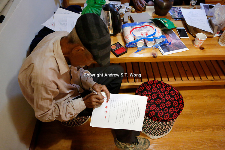 Wumu Village, Yulong County, Yunnan Province, China - An elderly villager signs documents prepared by Dongba priest He Jixian of the Naxi ethnic group during the inaugural meeting of their agricultural cooperative, June 2019
