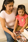 3 year old girl at home with mother looking at family photographs in album talking and interaction Mexican American vertical