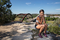Beautiful African-American athlete woman talking on smartphone on a cliff overlooking the 360 Bridge on Lake Austin, Texas.