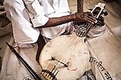 75-year-old Manganiyar artist and a Padmashree awardee, Saqar Khan tunes his Kamancha (music instrument) before the performance and field recordings inside his house in Hamira village of Jaiselmer district in Rajasthan, India. Photo: Sanjit Das/Panos