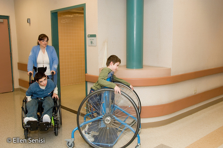MR / Albany, NY.Langan School at Center for Disability Services .Ungraded private school which serves individuals with multiple disabilities.Teaching assistant moves child in wheelchair while another child uses a Mobile Prone Stander to get back to the classroom. Children with cerebral palsy require varing degrees with toileting. Some may wear diapers; others may just need help getting onto the toilet. They are returning to classroom thru hallway after using the bathroom. Boy in green: 10, Duchenne muscular dystrophy, expressive and receptive language delays; Boy in blue: 11, cerebral palsy, expressive and receptive language delays.MR: Ber8; Bro12; Bud2.© Ellen B. Senisi