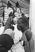 Kenya. Rift Valley province. Lokichogio. Storage room. Workers carry USA corn bags gifted to the World Food Programm (WFP) which will be later air-dropped as part as the Operation Lifeline Sudan.© 1998 Didier Ruef